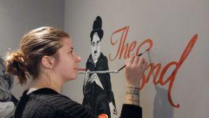 Johanna Karvonen målar Charlie Chaplin och The End på väggen i foajén på en biograf.