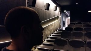 En man står i mörkret i en biosalong.