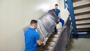 Två flyttjobbare bär ett skåp i ett trapphus.