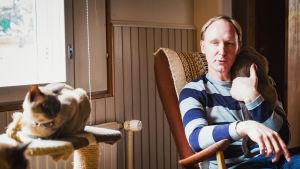 Oopperalaulaja Piers Bray istuu keinutuolissa olkapäällään burmankissa