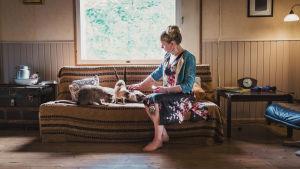 En kvinna sitter i en soffa med några katter.