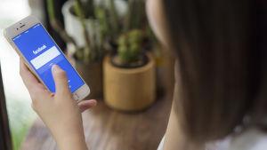En kvinna håller en smarttelefon i handen med Facebook öppen.