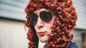 En man som bär solglasögon och är klädd i peruk.