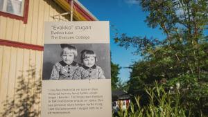 Kyltti, jossa vanha mustavalkoinen valokuva, jossa kaksi pikkutyttöä ja teksti Evakko-stugan, Evakko tupa, taustalla keltainen puutalo.