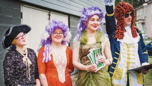 Esiintymisasuihin ja peruukkeihin pukeutuneet La Kalan jäsenet ottamassa vieraita vastaan.
