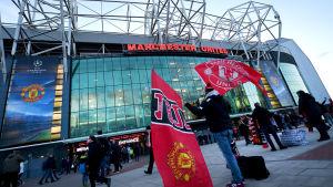 En supporter står utanför Old Trafford med två flaggor