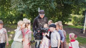 En skock med barn klädda i gammaldags kläder samlas runt fotografen Rasmus Tågs kamera.