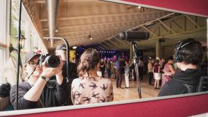 Fotografen Eva Pursiainen tar en bild av sig själv och övriga personer via en spegel inne i en danshall.