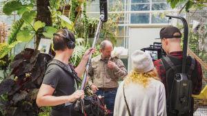 Ett inspelningsteam bestående av ljudman, regissör och fotograf står och filmar en man med en papegoja på axeln.