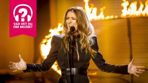 Celine Dion sjunger med armarna utsträckta åt sidorna.