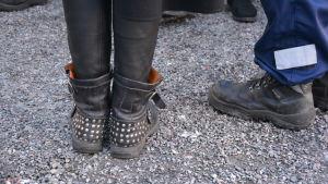 Ett par svarta skor med nitar och ett par polisskor.