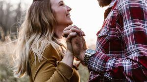 Pariskunta nauraa ja tanssii käsikädessä
