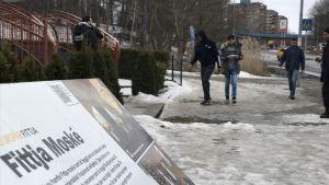 Infomrationsplakat om Fittja moské, i bakgrunden unga män påväg till moskéen.