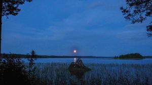 Sinertävä tyyni järvenselkä, auringonlasku.