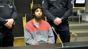 Marockanen Abderrahman Bouanane sitter i rätten med två säkerhetsvakter som står bredvid.