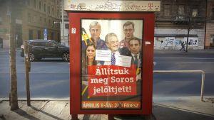 """En kampanjposter för Fidesz och mot oppositionen och George Soros. Texten lyder  ungefär """"Hjälp oss stoppa Soros hantlangare""""."""