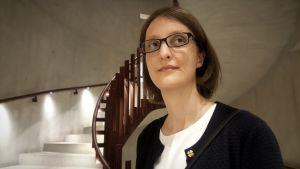 Statsvetaren Sara Svensson står i en grå trappuppgång.