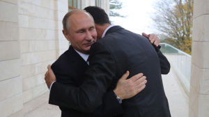 Vladimir Putin omfamnar Bashar al-Assad.