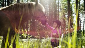pieni tyttö taputtaa hevosta turvalle niityllä, aurinkoisen metsän reunassa