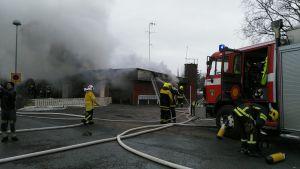 Brandmän sprutar vatten mot det brinnande huset.