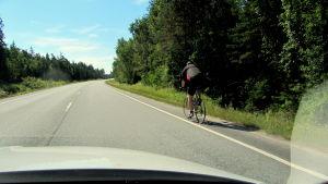 En landsvägscyklist blir omkörd av en personbil.