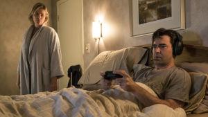 Marlo står vid dörren till sängkammaren där maken Drew ligger och spelar tvspel.