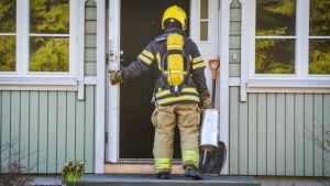 Brandman på väg in i hus