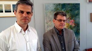 Två män står framför några tavlor.