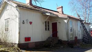 En ljus gammal träbyggnad på en innergård.
