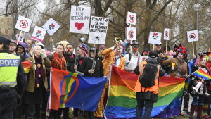 """Motdemonstranter håller upp regnbågsflagga och plakat där det bland annat står """"Folk mot hetsgrupp""""."""