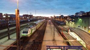 Ett grönvitt tåg är klart att starta från Åbo järnvägsstation. I bakgrunden finns Logomo och gångbron som byggs över järnvägen.