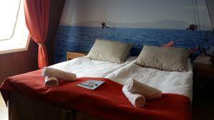 Fartygshytt med rostbrunt täcke och ett foto med en segelbåt på väggen på m/s Finnswan.