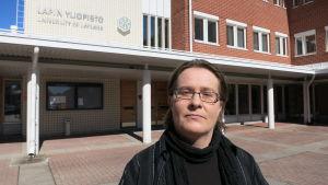 Aini Linjakumpu står framför Lapplands universitet där hon forskar i statsvetenskap.
