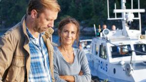 Karaktärerna Thomas och Nora på en brygga med en polisbåt i bakgrunden.