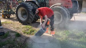 Kristoffer Nilsson putsar luftfiltret till sin traktor