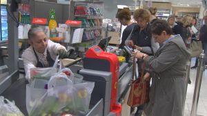 Flera damer i kö vid en kassa i en livsmedelsaffär.