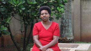 Mörkhyad kvinna i röd klänning sitter på en bänk och tittar in i kameran.