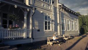 Valkoinen, vanha rautatieasema, jonka edustalla istuu nainen.