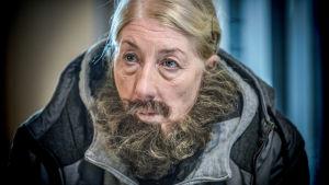 Kvinnlig bankrånare med lösskägg i tv-serien Enkelstöten. Spelad av Lotta Tejle.