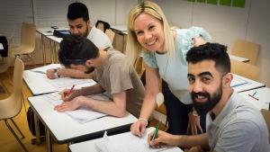 Opettaja katsoo oppilaan vihkoa.