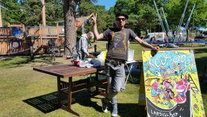 Marko Niemi står vid ett bord i en lekpark, redo att dela ut gratis mat till barn.