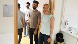 Opettaja seisoo luokan ovella ja oppilaat tulevat luokkaan