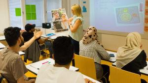 Opettaja näyttää oppilaille sanomalehden etusivua