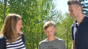 mia och adam och magnus nyholm står bredvid varandra utomhus. I bakgrunden står björkar.