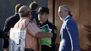 Polisen stoppade en demonstrant som försökte närma sig affärmannen Francisco Correa (till höger) inför en rättegångssession i Madrid den 10 oktober 2016.