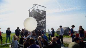 Folksamling väntar på att en väderballong ska släppas upp.