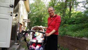 ung mamma med röd blus står med baby i barnvagn utanför ett trähus vid en grönskande park