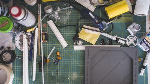 Ett arbetsbord med en mängd små verktyg, penslar, färger och lim.