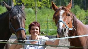 Maria Groundstroem tittar in i kameran och ler, hon har två hästar vid sin sida.