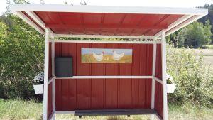 Busskuren i Hönsnäs i Houtskär är målad i rött, med en bild av hönor och kycklingar på väggen.